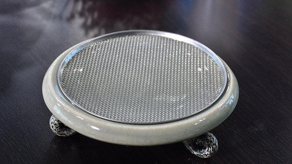 Auf einem Tisch steht ein heller Keramikteller mit einem Metallsieb
