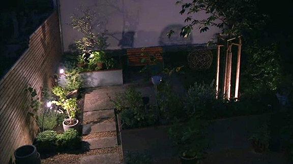 Ein mit elektrischen Lampen beleuchteter Garten in einem Innenhof bei Nacht