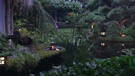 Ein mit elektrischen Lampen und einer Flamme beleuchteter Garten mit einem Teich bei Nacht