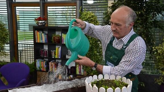 Mann gießt Blumenkästen