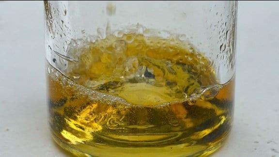 In einer Flasche ist goldfarbener Schnaps