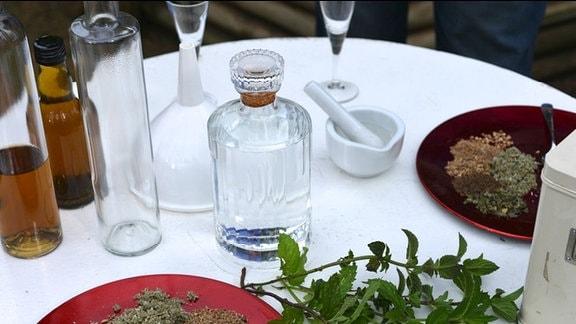 Verschiedene Zutaten und Utensielien stehen auf einem Tisch, Teller,Flaschen,Mörser,Kräuter