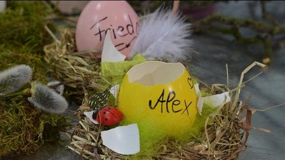 In der Mitte eines mit Moss umwickelten Kranzes steht ein leeres Ei. Auf dem Ei steht ein Name