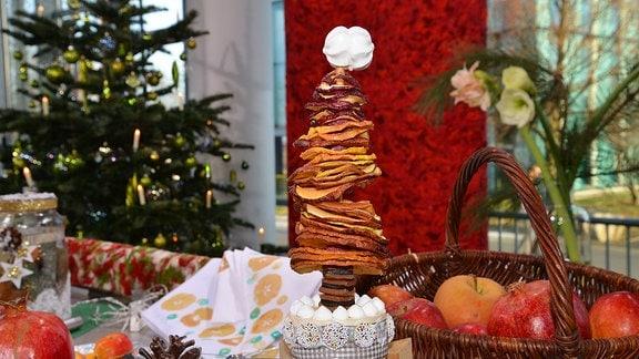 Auf einem Tisch steht ein Weihnachtsbaum aus Apfelsinenscheiben. Die getrockneten unterschiedlich großen Scheiben wurden auf einen Holzstab aufgefädelt. Die kleinen Scheiben sind oben, die großen unten.