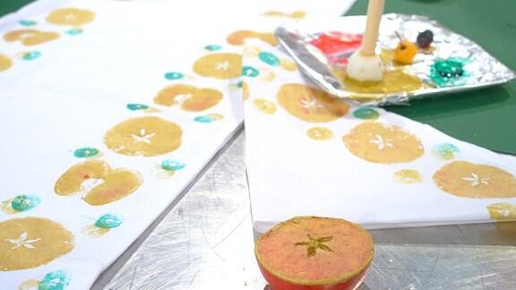 Auf einem Tisch liegt ein weißes Leinentuch. Es wurde mit Hilfe von halben Äpfeln bedruckt. Im Vordergrund liegt ein aufgeschnittener halber Apfel mit goldener Farbe.