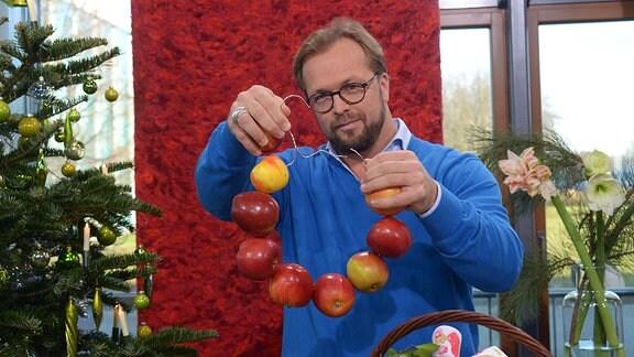 Moderator Jens Haentzschel hält einen Drahtkleiderbügel in der Hand auf dem viele Äpfel aufgefädelt sind.
