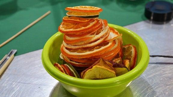 In einer Schale liegen getrocknete Apfelsinenscheiben.