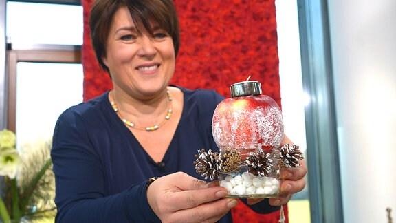 Eine Frau hält einen dekorierten Apfel. Auf dem Apfel steht eine Kerze.