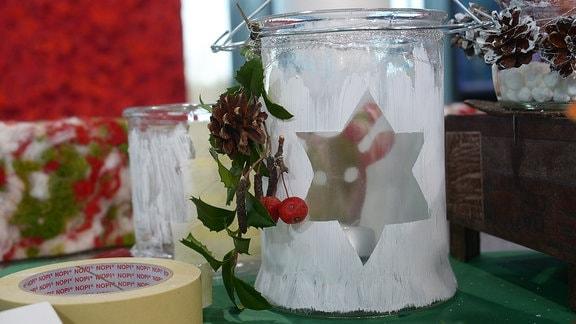 Ein Glas mit einem ausgesparten Elch ist mit weißer Farbe bemalt.