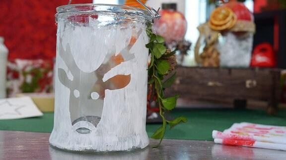 Ein Glas mit einem ausgesparten Stern ist mit weißer Farbe bemalt.