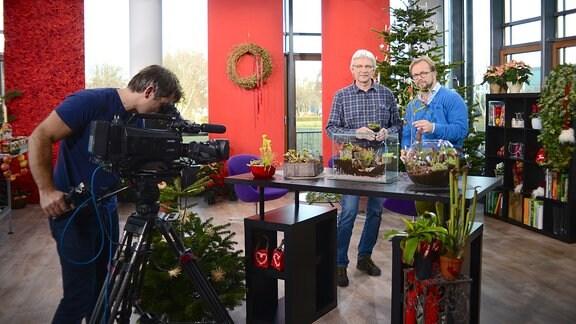 Zwei Männer stehen vor einem Tisch mit Pflanzen.