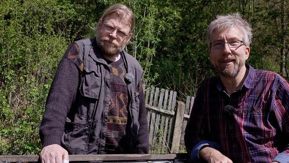Zwei Männer stehen hinter einem Hochbeet.