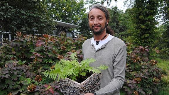 Der Gartenjournalist Martin Staffler steht mit einem Topf mit einem Straußenfarn darin im egapark in Erfurt