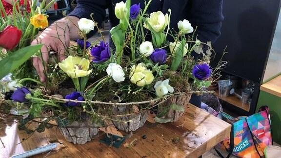 In kleinen Blumentöpfen in Holzoptik wurden lila und weiße Blumen mit Zweigen arrangiert.