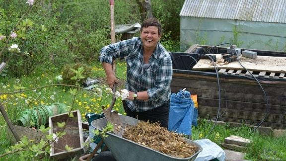 Obstbaumexpertin steht hinter einer mit Mulch gefüllten Schubkarre