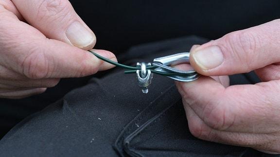 Ein Draht wird um eine Öse befestigt