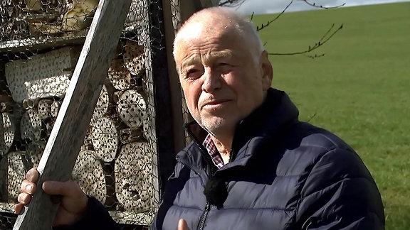 Hobby Insektenforscher vor einem Insektenhotel