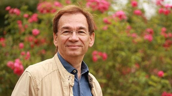 Redaktionsleiter des MDR Gartens Michael Wenkel in einem Park mit Blumen.