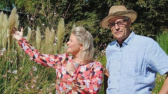 Gärtner Host Schöne und Moderatorin Diana Fritzsche-Grimmig stehen in einem Gräsergarten und reden