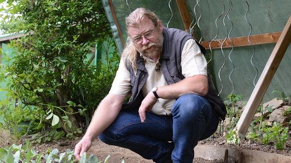 Gärtner Martin Krumbein hockt an einem Gemüsebeet mit Salaten