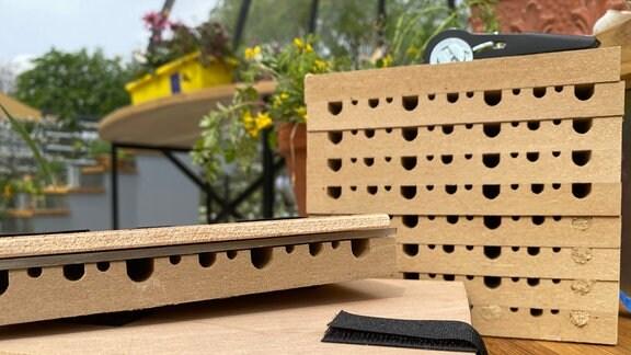 Ein Nistblock für Wildbienen: mehrere Bretter mit Löchern  wurden übereinandergestapelt.