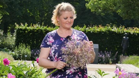 Diana Fritzsche-Grimmig hält die riesige Blüte eines Steinkugellauchs in den Händen.