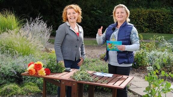 MDR Garten-Expertin Brigitte Goss und MDR Garten-Moderatorin Diana Fritzsche-Grimmig an einem Holztisch im Egapark Erfurt