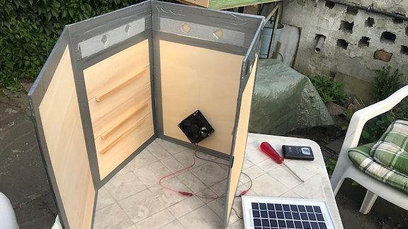 Auf einem Tisch steht Material, das zum Bauen eines Dörrgerätes gebraucht wird.