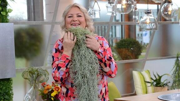 Moderatorin Diana Fritzsche-Grimmig hält sich eine Tillandsia ans Kinn. Die hängende Pflanze reicht bis zum Boden.