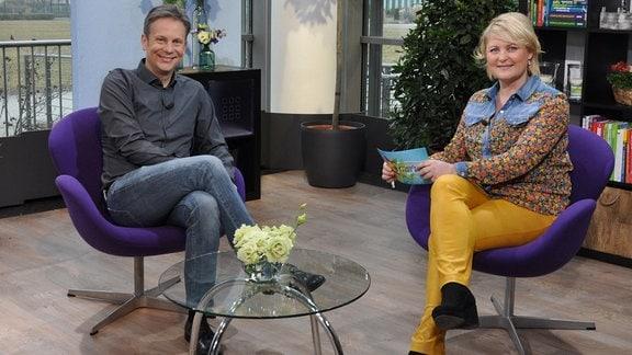 Ein Mann und eine Frau sitzen auf lila Sesseln. Sie lächeln in die Kamera. Vor ihnen steht ein Glastisch.
