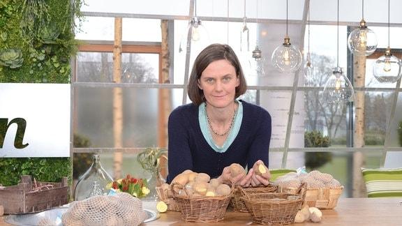 Eine Frau steht hinter einem Pflanztisch auf dem verschiedene Kartoffelsorten liegen.