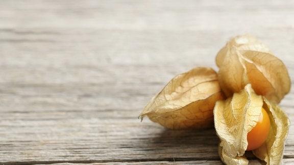 Auf einem Holzbrett liegen drei Physalis-Früchte