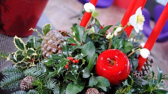 Ein weihnachtliches Gesteck mit verschiedenen, immergrünen Zweigen, Zapfen, einem roten Apfel aus Kunststoff, einer weiß blühenden Christrose und langen, roten Kerzen