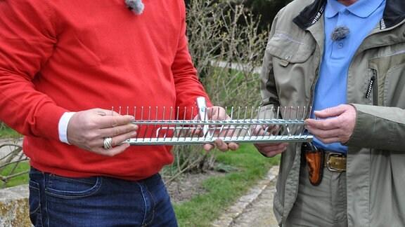Ein Aufsatz für eine Stiel, der wie ein Rechen aussieht. Zusätzlich trägt er zwischen den Zinken eine bewegliche Schiene.