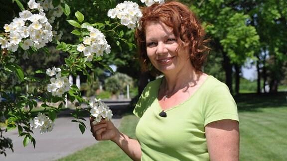 Eine Frau mit halblangen rot-braunen Haaren lächelt in die Kamera. Sie trägt ein hellgrünes T-Shirt und steht neben einer Pflanze mit weißen Blüten.