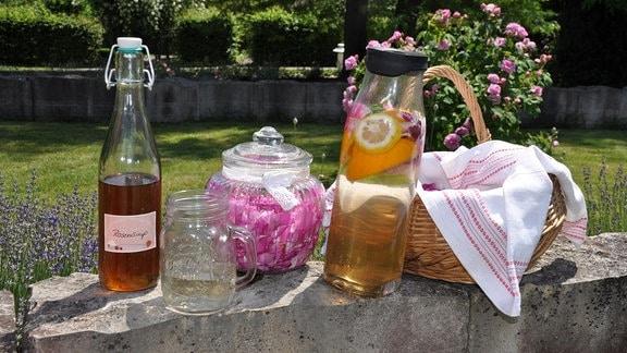 Auf einer Mauer stehen eine Flasche mit Sirup, ein Henkelglas mit Flüssigkeit, ein Glasgefäß mit Deckel und Rosen, eine Karaffe mit Früchten und Flüssigkeit sowie einem Körbchen.