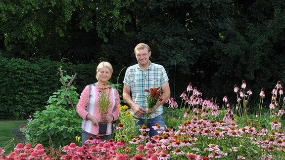Ein Mann und eine Frau stehen hinter einem Beet mit ganz vielen blühenden Blüten.