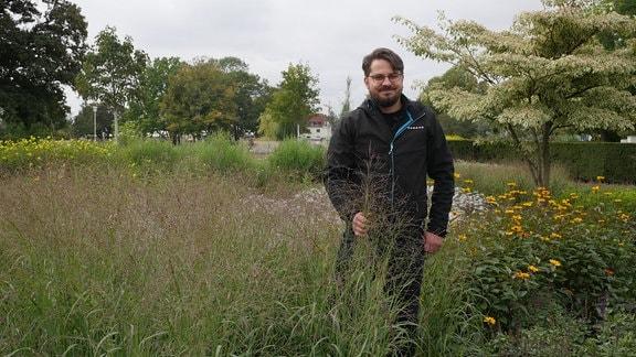Gärtner Daniel Zugwurst steht neben Rutenhirse.