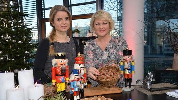 Zwei Frauen stehen hinter einem Tisch mit Nüssen und Nussknackern.