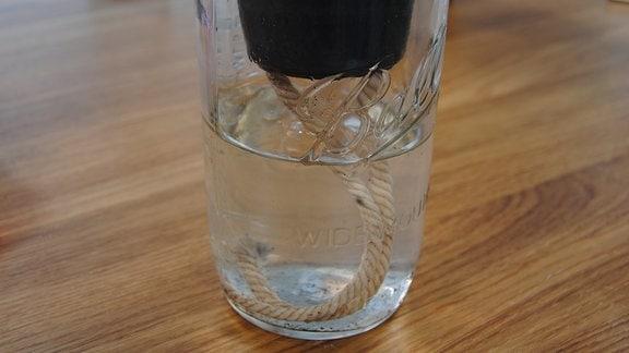 Kordel hängt aus Blumentopf in Wasserglas darunter