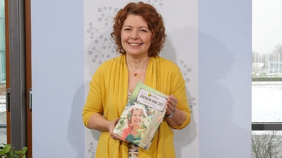 Brigitte Goss lächelt in die Kamera und hält ihr Buch in den Händen.