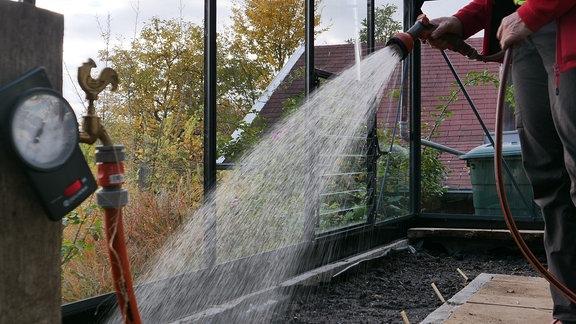 Gießen mit Gartenschlauch in Gewächshaus