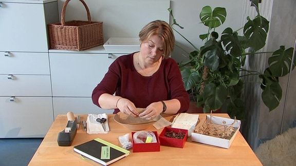 Eine Frau sortiert Samen an einem Tisch.