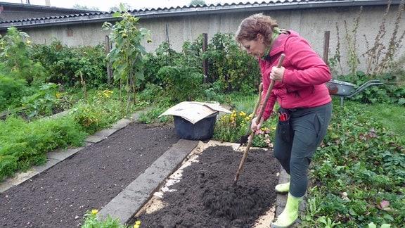Gärtnerin Brigitte Goss verteilt Erde auf Pappe in Beet Brigitte Goss und Jens Haentzschel jäten Unkraut in Beet Erde auf Pappe auf einem Beet
