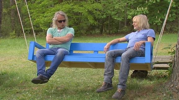 Eine Schaukel aus Holz zwischen zei Bäumen, darauf sitzend: zwei Männer.