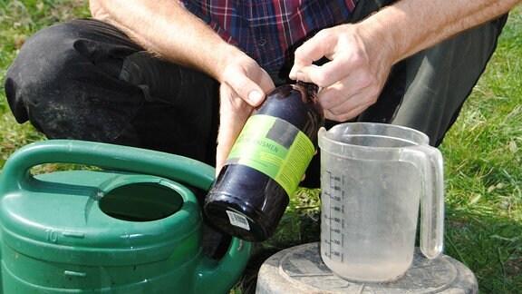 MDR Garten-Redakteur Jörg Heiß hockt in seinem Kleingarten neben einer Gießkanne und hält eine braune Flasche mit einer Flüssigkeit, in der verschiedene Bakterien und Pilze enthalten sind,
