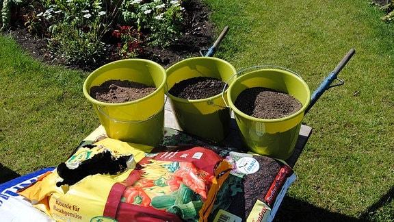 Drei grüne Plastikeimer mit Erde und mehrere Säcke Substrat für Blumen und Gemüse auf einer Schubkarre, die auf einer Wiese steht.