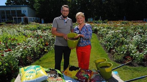 Falko Windisch vom Kalk- und Erdenwerk Herbsleben steht neben MDR Garten-Moderatorin Diana Fritzsche-Grimmig mit einem grünen Plastikeimer voller Erde vor einer Schubkarre mit mehreren Säcke Substrat für Blumen und Gemüse auf einer Wiese im Egapark Erfurt.
