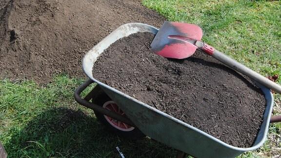 Schubkarre mit Mischung aus Erde und Kompost