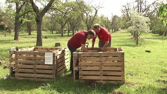 Zwei Kompostbehälter stehen nebeneinander. Zwei Männer beugen sich darüber.